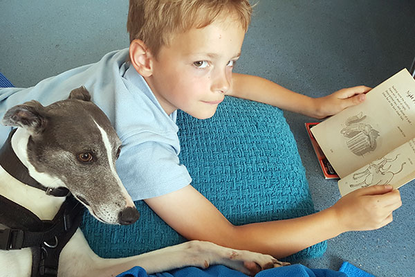 Boy reading book with a dog